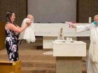 bapteme bebe a l'église le pretre asperge l'eau benite avec un pistolet a eau
