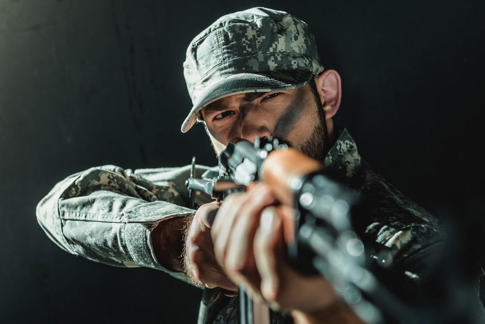 Un homme vêtu d'une tenue militaire, avec un fusil.