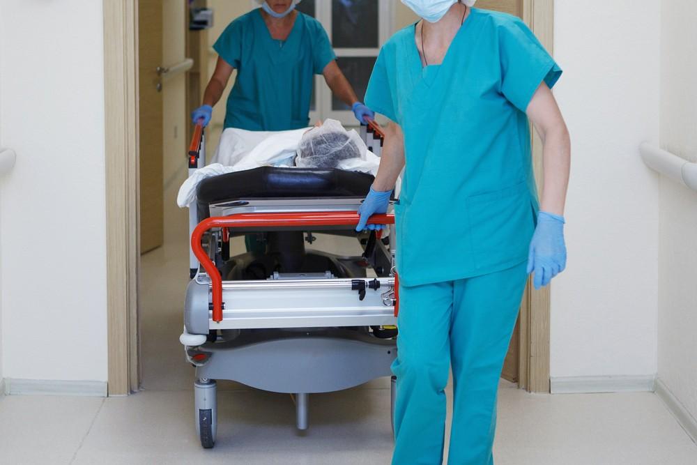 Des infirmiers poussant un lit d'hôpital.