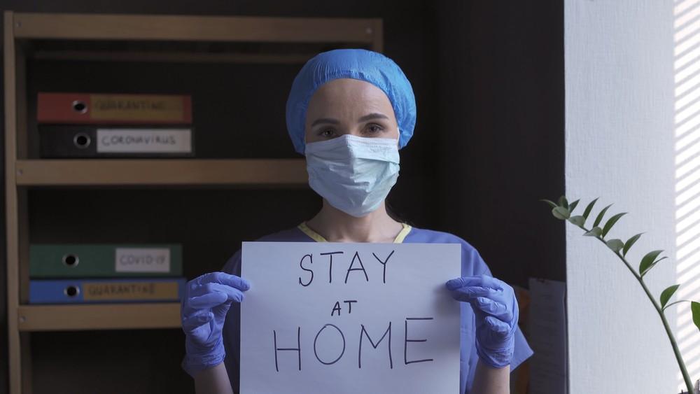 Une infirmière demandant aux gens de rester chez eux.