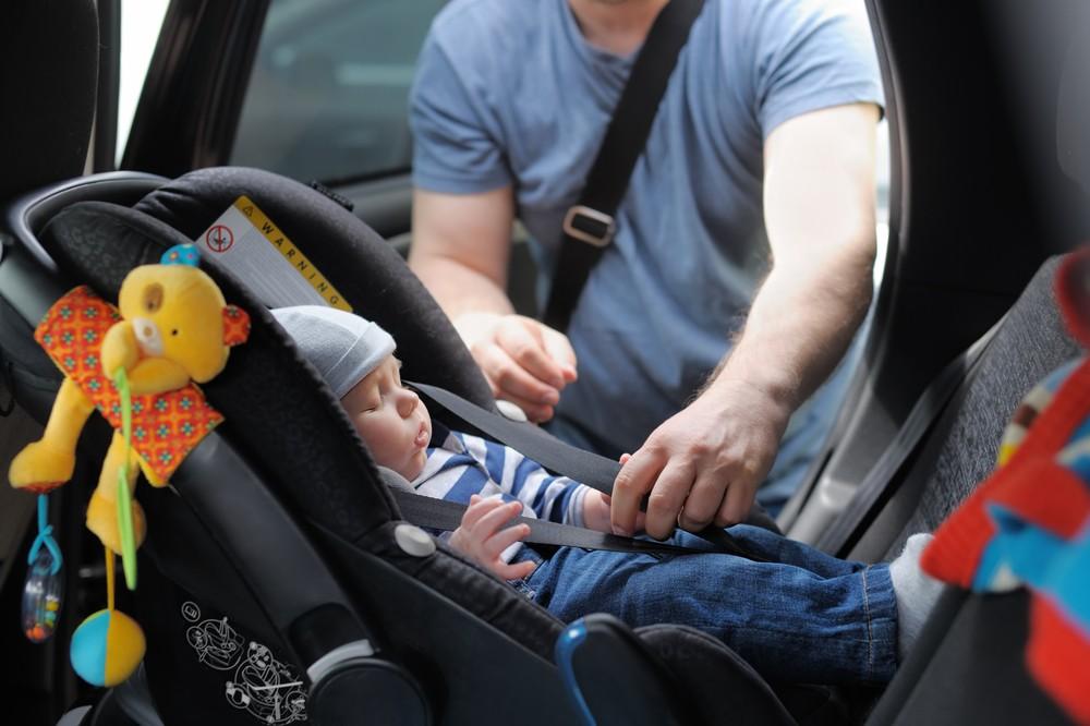 Un père de famille avec son bébé dans le siège auto.