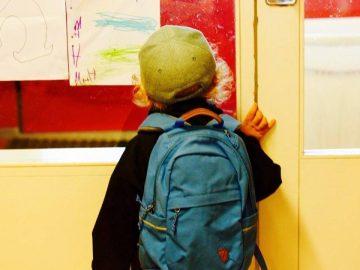 Un écolier devant sa salle de classe.