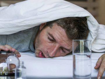Un homme désaoulant dans son lit.
