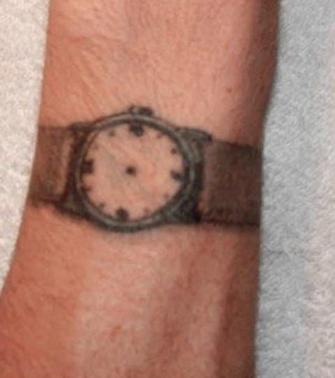 Une montre sans aiguilles tatouée sur le poignet.