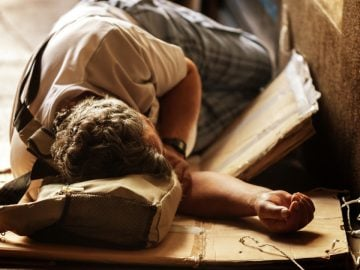 Un jeune SDF qui dort au sol.