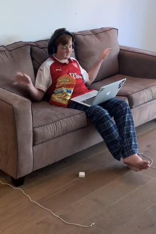 Un écolier en télétravail mange des bonbons