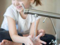 Enfant se lave les mains dans le lavabo
