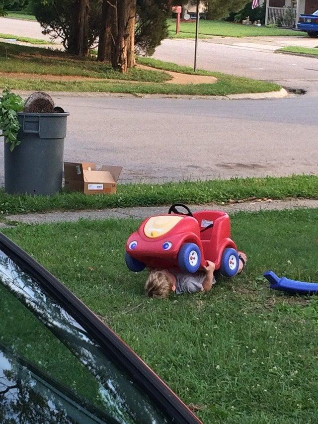 Un enfant joue à cache-cache en se cachant sous une voiturette.