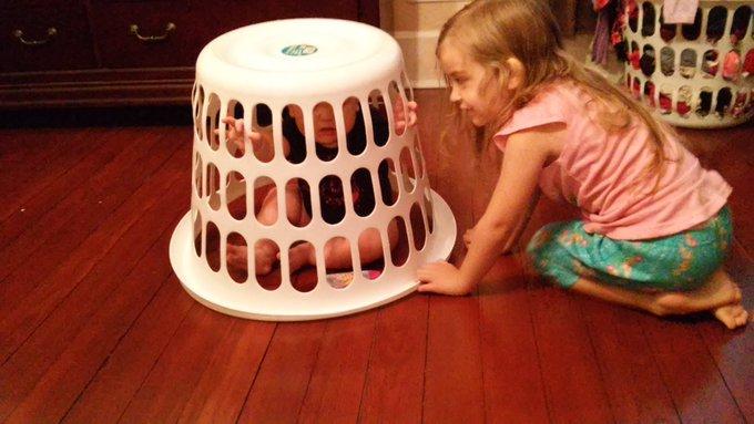 Une petite fille contente d'avoir piégé son frère sans un panier à linge sale.