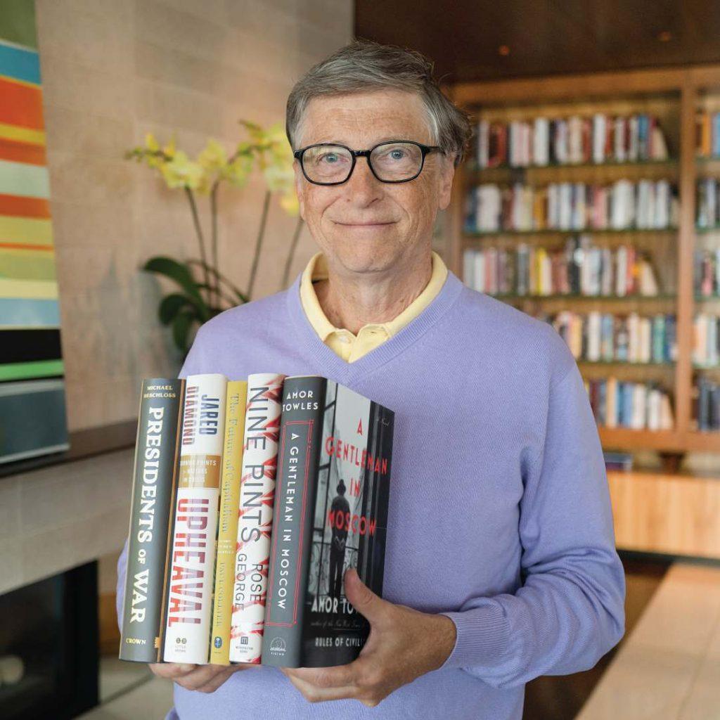 Bill Gates tient des livres dans la main