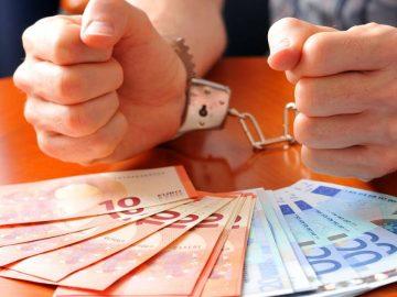 une personne menottée devant des billets de banque