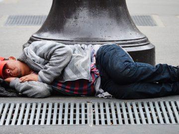 Un sans abris dort dans la rue.
