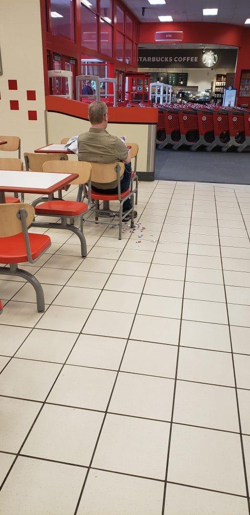 un homme jette des emballages de bonbons par terre