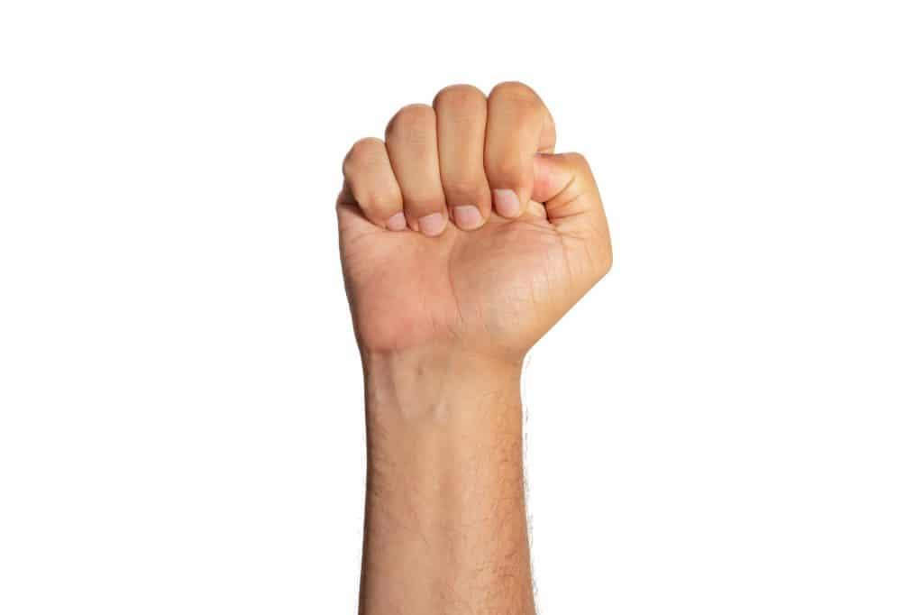 Poing serré avec pouce sous les autres doigts