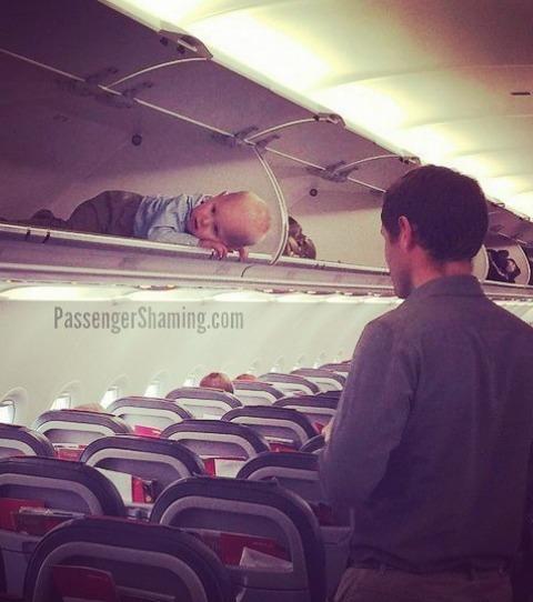 Un bébé dans le porte bagage d'un avion