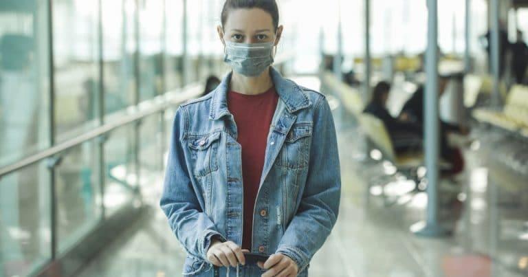 Une jeune femme qui voyage avec un masque