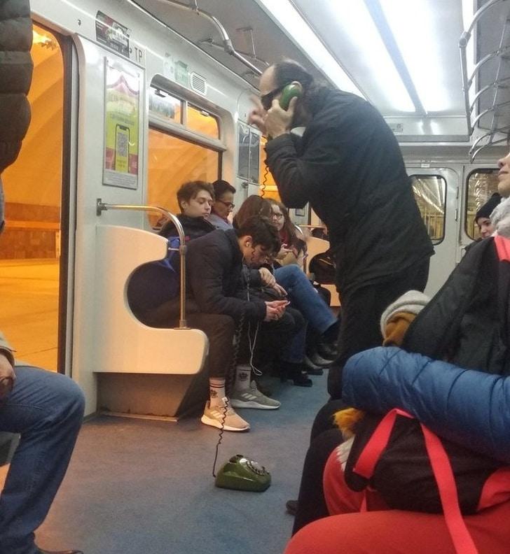 Un homme qui téléphone avec un ancien téléphone dans le métro