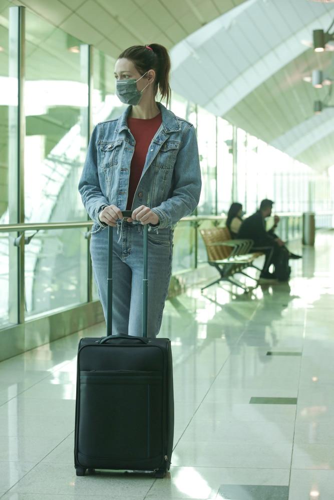 Une voyageuse avec un masque à l'aéroport