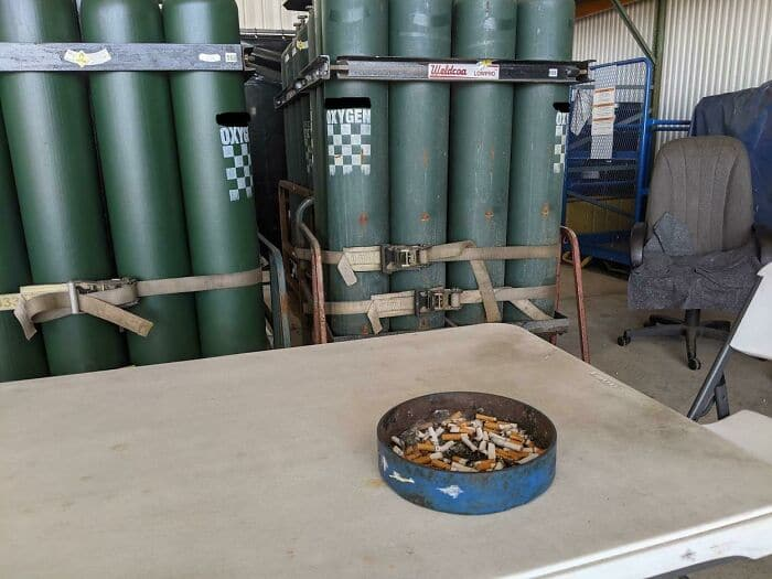 un cendrier à côté de bonbonnes de gaz