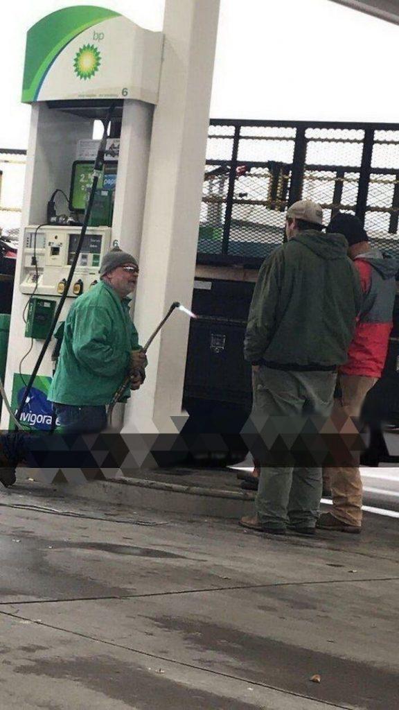 un travailleur avec un chalumeau dans une station essence