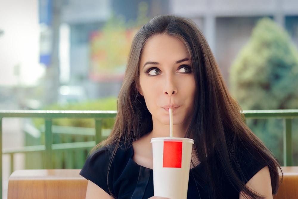 une femme qui boit des sodas diététiques