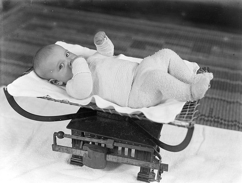 un bébé pesé avec une balance de boucherie en 1936