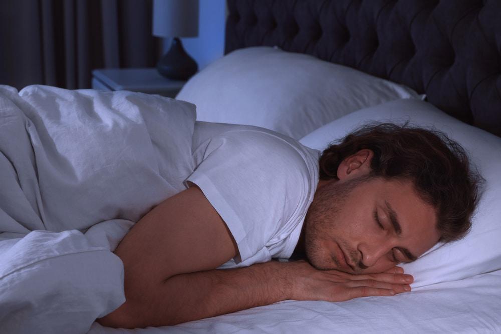 un homme qui dort avec un drap quand il fait chaud